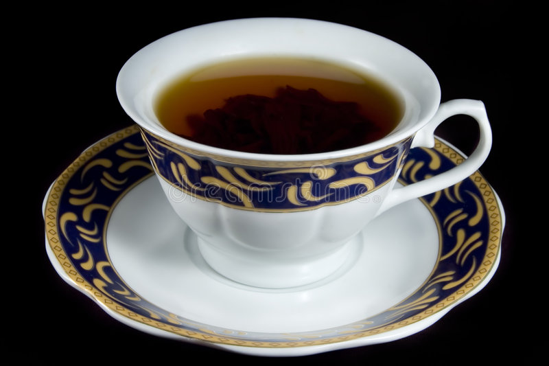Tea. Cup of tea with tea leaves on a black background royalty free stock image