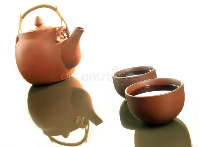 Tea. An Asian teapot with green tea in cups royalty free stock image
