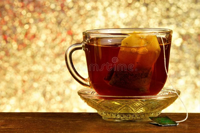 Tea in a bag in a Cup on a saucer, against the background of rainbow lights bokeh. Helpful tea is popular refreshing drink. Obtained by boiling and macerating royalty free stock photo