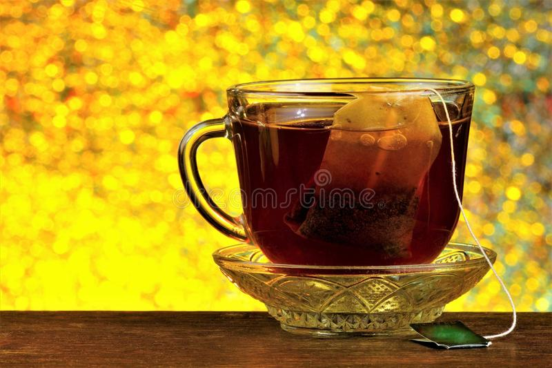 Tea in a bag in a Cup on a saucer, against the background of rainbow lights bokeh. Helpful tea is popular refreshing drink. Obtained by boiling and macerating stock photos
