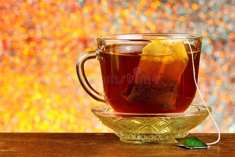 Tea in a bag in a Cup on a saucer, against the background of rainbow lights bokeh. Helpful tea is popular refreshing drink. Obtained by boiling and macerating royalty free stock images