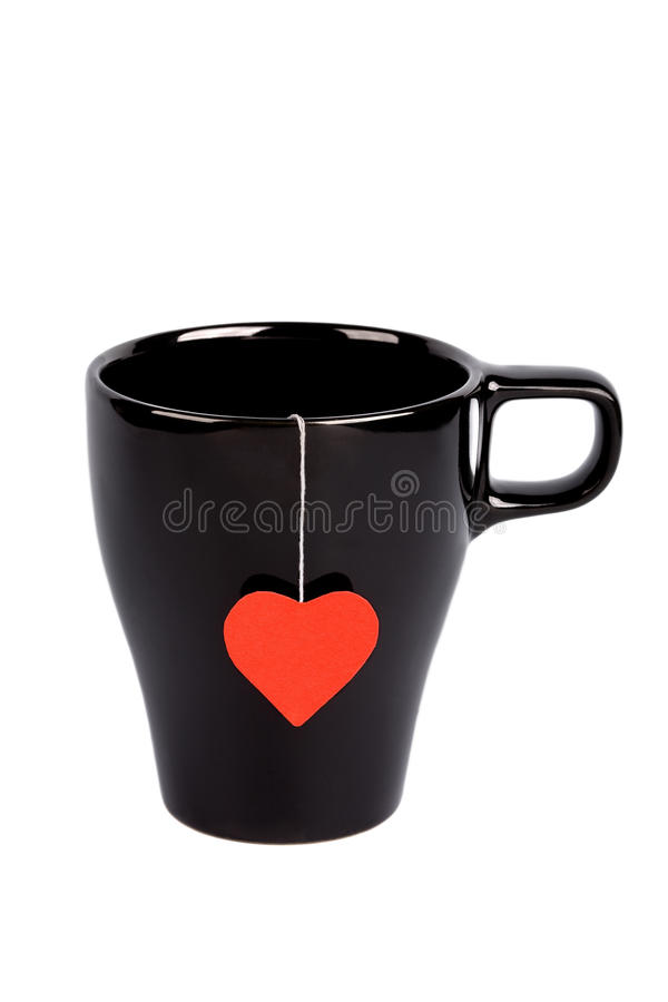 Tea bag with heart-shaped label in cup isolated royalty free stock photography