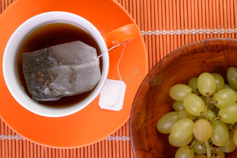 Tea bag infusing in cup Grapes Healthy snack stock image