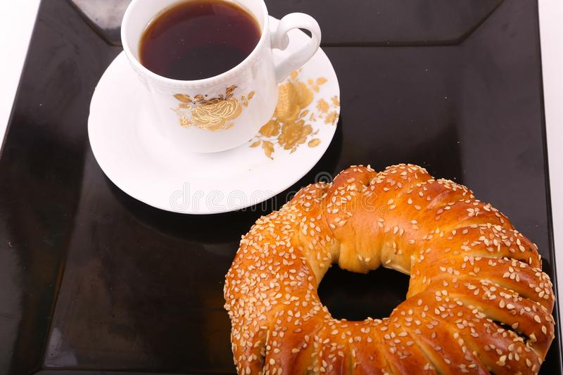 Tea with bagel. Bagel with cup of tea on modern black dish over white background stock photos