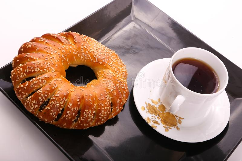 Tea with bagel. Bagel with cup of tea on modern black dish over white background stock image