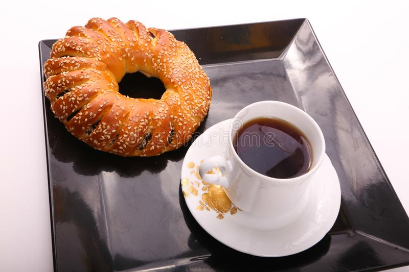 Tea with bagel. Bagel with cup of tea on modern black dish over white background royalty free stock images