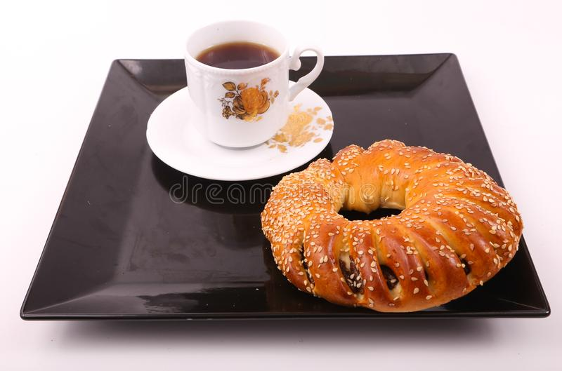 Tea with bagel. Bagel with cup of tea on modern black dish over white background royalty free stock image