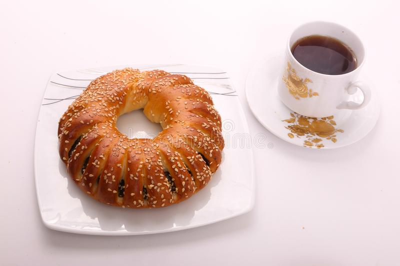 Tea with bagel. Bagel with cup of tea on modern white dish over white background stock photography