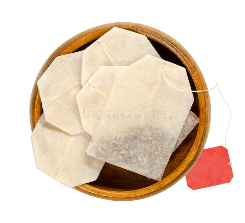 Tea bags, made of filter paper, with tea in a wooden bowl royalty free stock photos