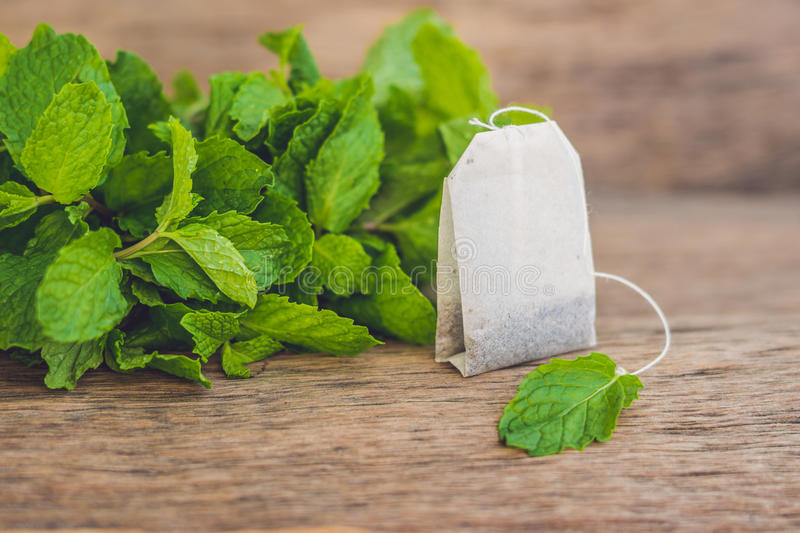 Tea bags on wooden background with fresh melissa, mint. Tea with mint concept royalty free stock image