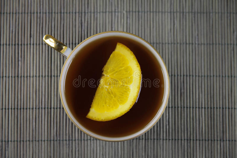 Tea on the bamboo background. Tea with orange on the bamboo background royalty free stock image