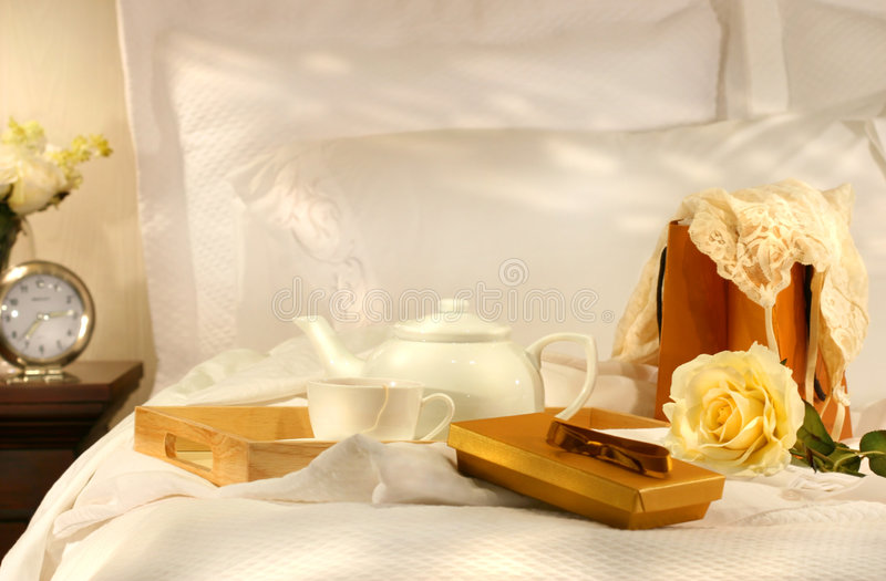 Tea in bed with chocolates stock image