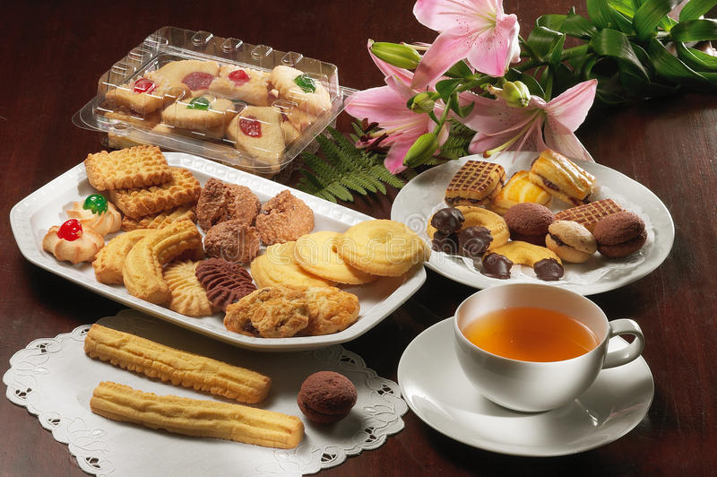 Tea and biscuits. Afternoon tea and biscuits ona table with a flower and a doily stock photo