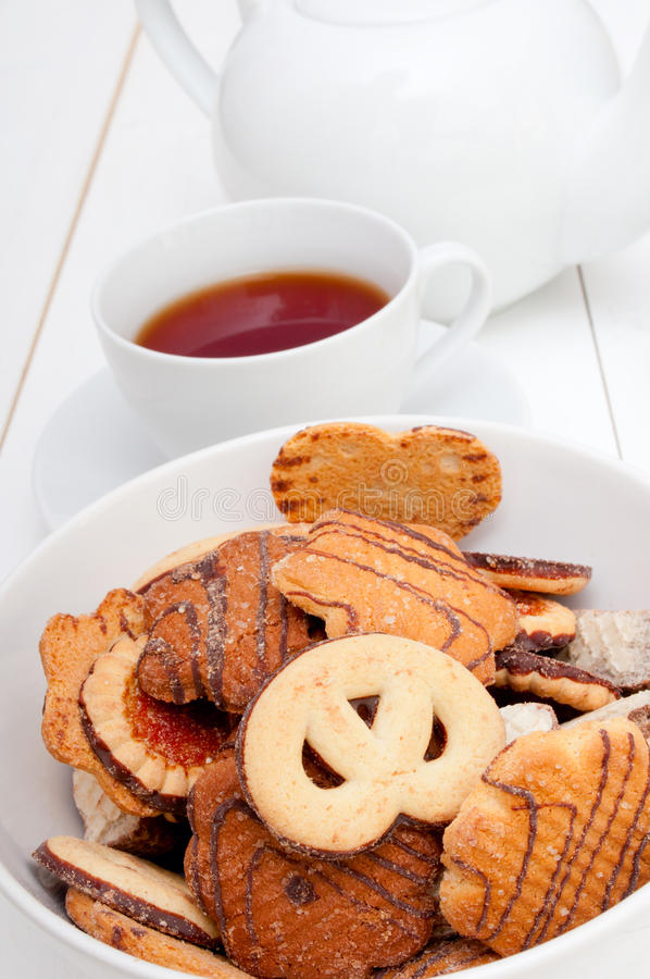 Tea and Biscuits. White Cup of Tea, Biscuits and Teapot on White Table royalty free stock photos