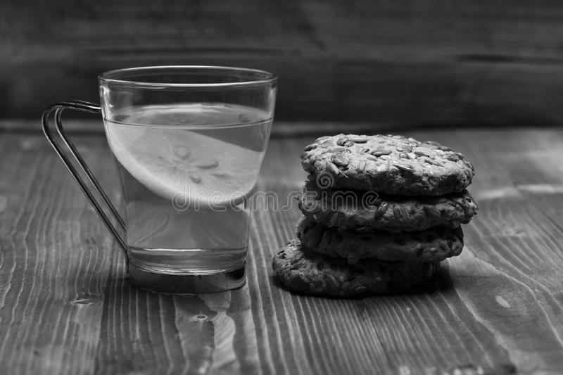 Tea and biscuits. Traditional snack for tea time. Drink and homemade goods. Concept. Cookie made of oatmeal and tea cup with lemon on wooden background stock image
