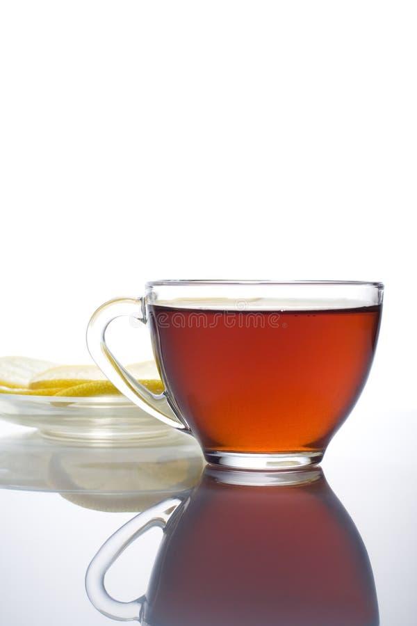 Tea break. Cup of hot tea with lemon on saucer stock photo