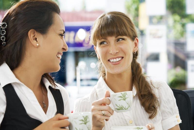 Tea break. Portrait of young pretty women having coffee break in office environment stock image