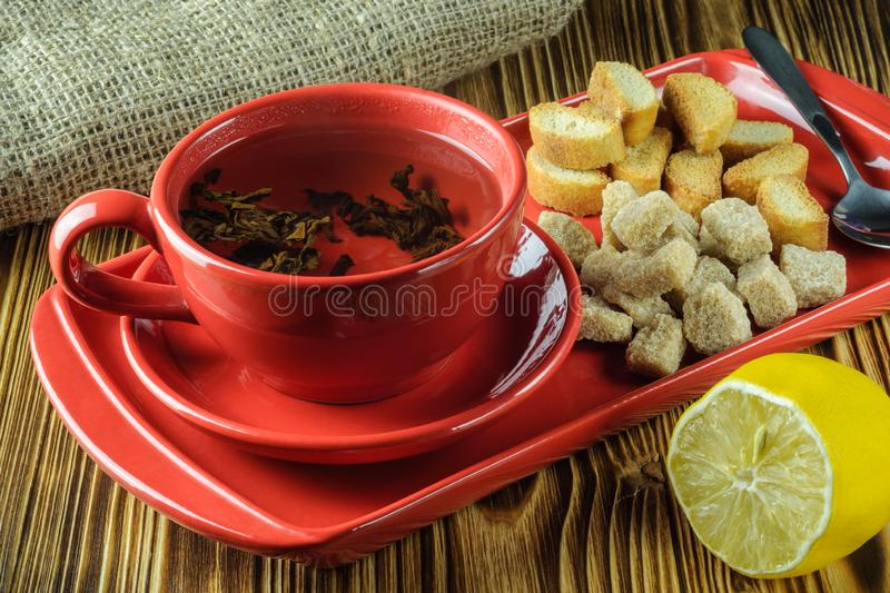 Tea break. tea in a red ceramic dish on a tray with cane sugar, crackers and lemon on a wooden background. angle view. Tea break. Tea in a red ceramic cup on a stock photo