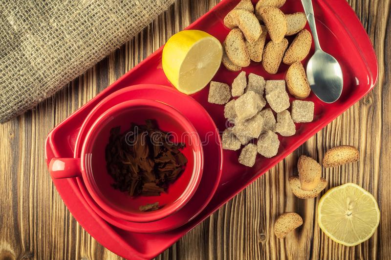 Tea break. tea in a red ceramic dish on a tray with cane sugar, crackers and lemon on a wooden background. top view. Tea break. Tea in a red ceramic cup on a royalty free stock images