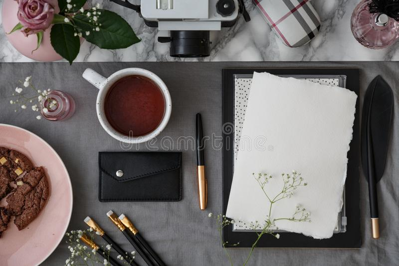 Tea, business card case, fine brushes, pen and sheet of paper on a desk. Top view stock photography