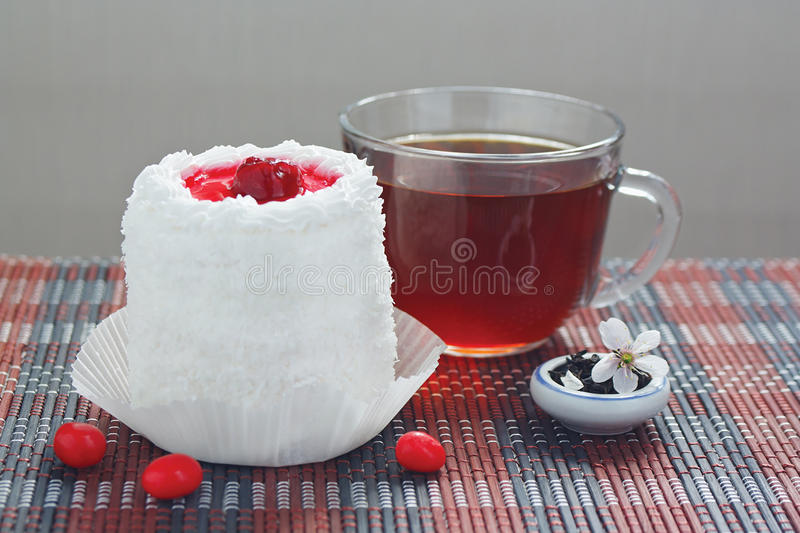 Tea, cake with cherries and jar of tea leaves royalty free stock photography