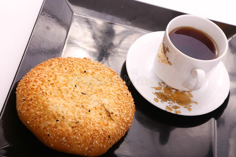 Tea with cake with sesame. Cake with sesame with cup of tea on modern black dish over white background royalty free stock image
