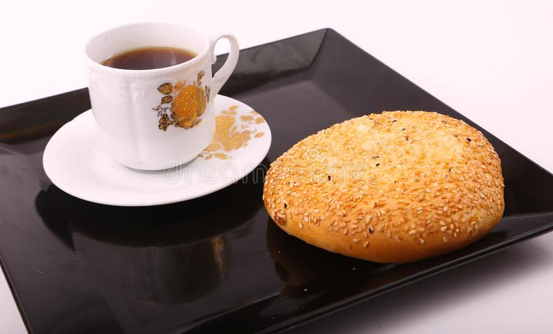 Tea with cake with sesame. Cake with sesame with cup of tea on modern black dish over white background royalty free stock photo