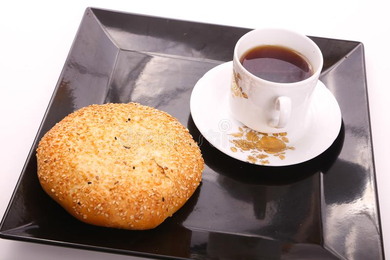 Tea with cake with sesame. Cake with sesame with cup of tea on modern black dish over white background royalty free stock images