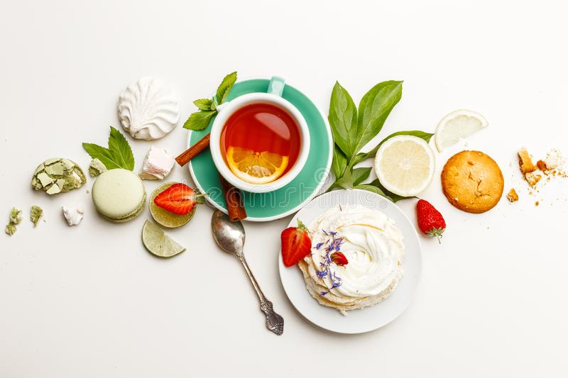 tea with cakes, and fruit on a white table royalty free stock photo