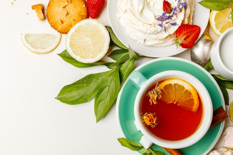 tea with cakes, and fruit on a white table royalty free stock photos