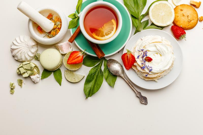 tea with cakes, and fruit on a white table stock photo