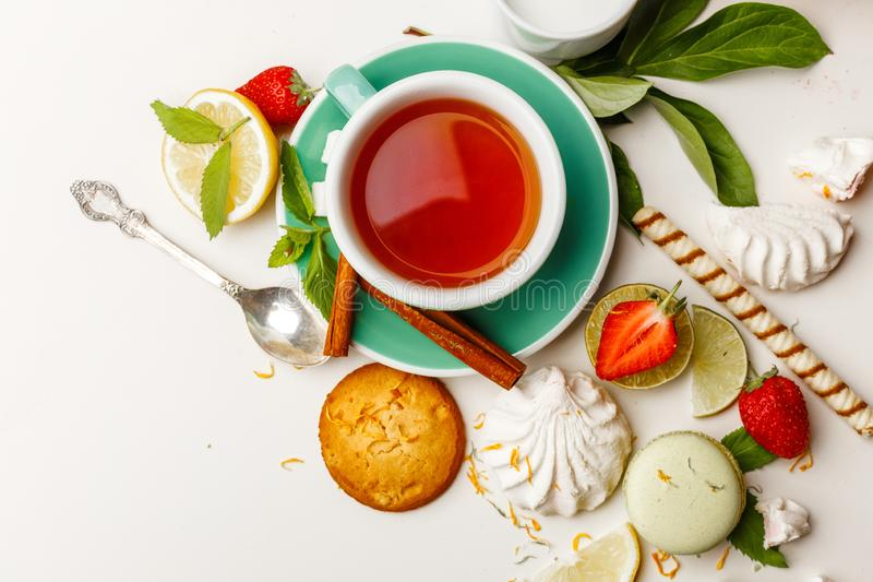 tea with cakes, and fruit on a white table stock photos
