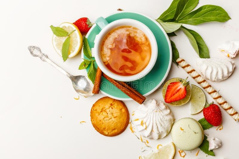 tea with cakes, and fruit on a white table royalty free stock images