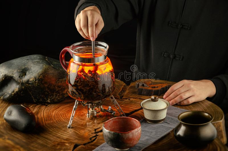 Tea ceremony brewing tea on fire in a glass teapot. The tea ceremony brewing tea on fire in a glass teapot stock image