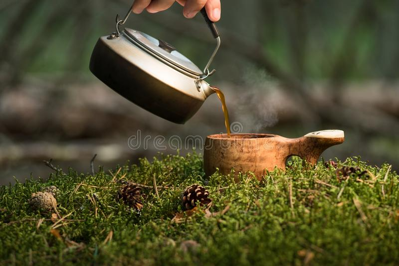 Tea ceremony at the taiga. Mini kettle and wooden bowl on a moss stock photos