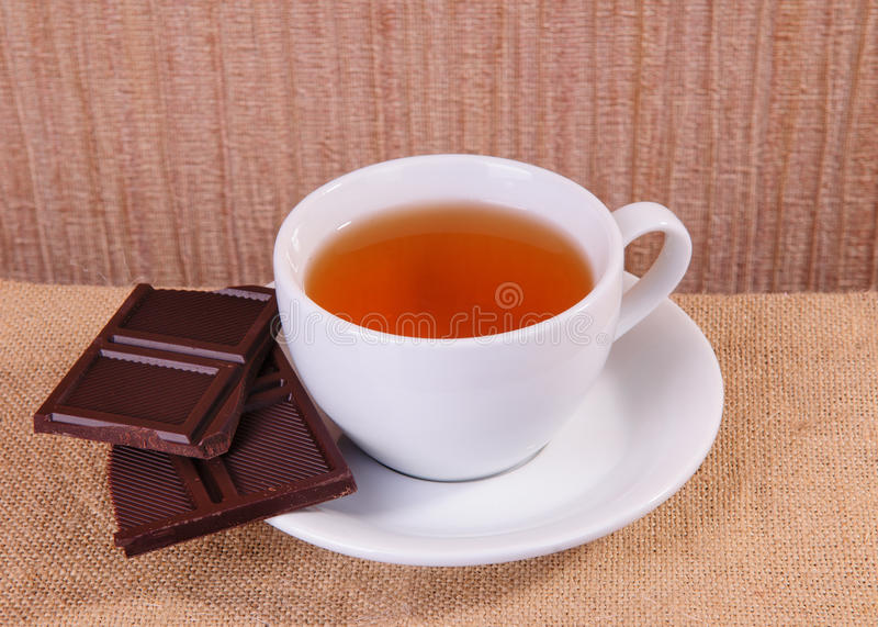 Tea and chocolate. White cup of hot tea and chocolate on sacking stock photography