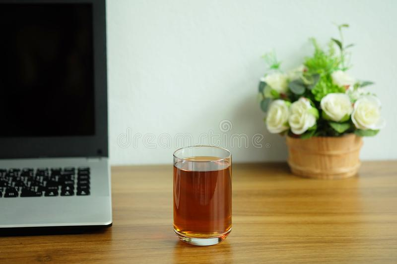 Tea in a clear glass on a wooden office desk with laptop computer, Tea afternoon break royalty free stock images