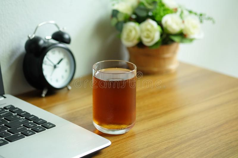Tea in a clear glass on a wooden office desk with laptop computer, Tea afternoon break stock photography