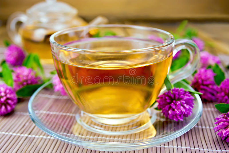 Tea with clover in cup on bamboo stock photos