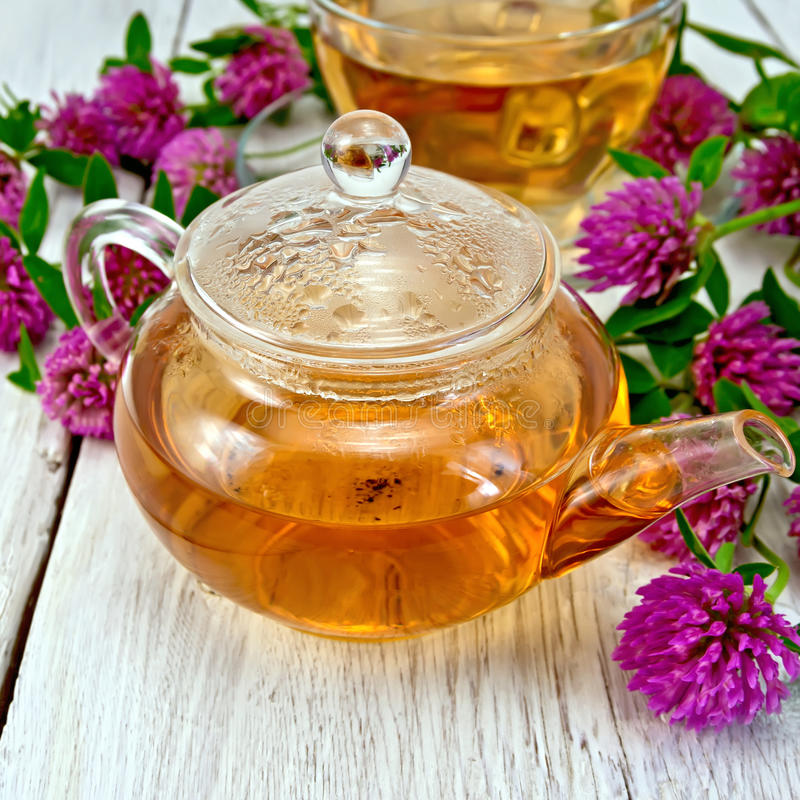 Tea with clover in glass teapot on board royalty free stock images