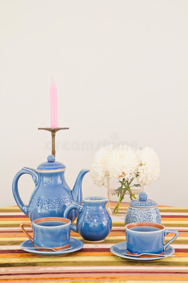Tea or coffee set on table. With colorful line fabric in gray wall room stock photo