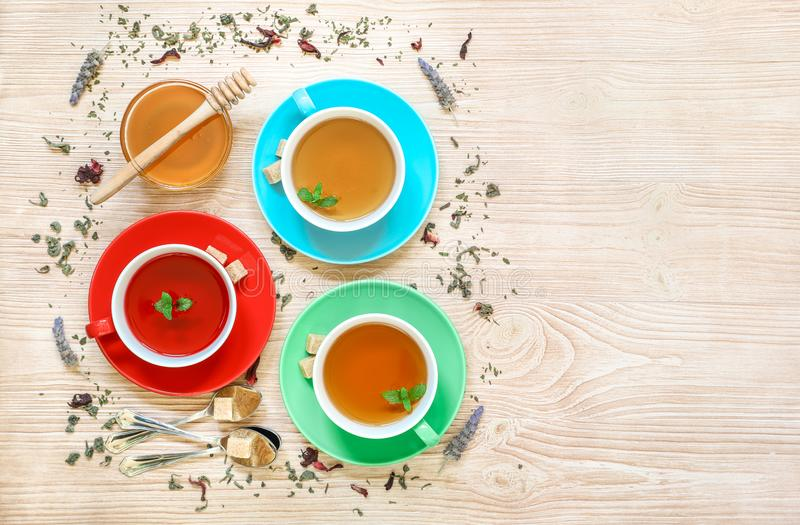Tea Collection of three different types of tea - mint, hibiscus and herbal tea in cups on wood background. stock photo