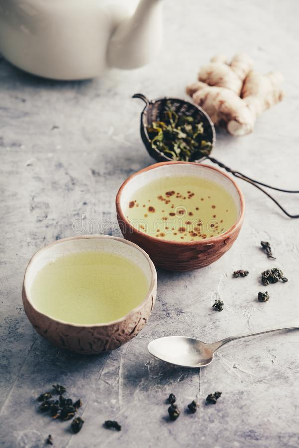 Tea composition with old chinese cups of green tea and white teapot royalty free stock image