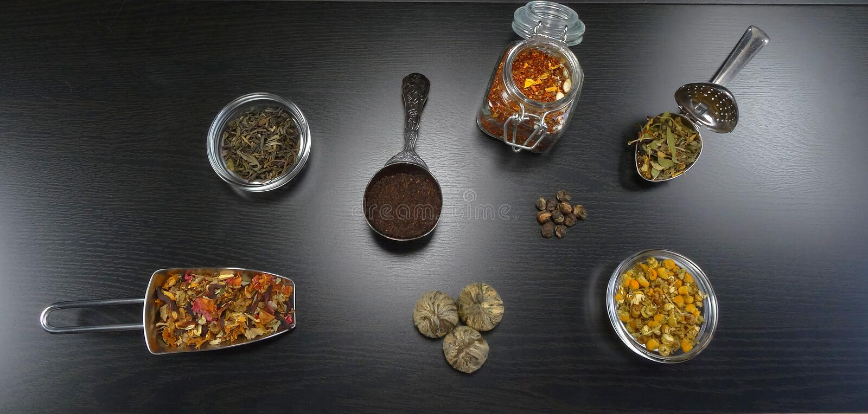 Tea composition with real tea and tea flowers, jasmine, chamomile, black tea, health tea at black wooden background stock image