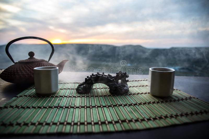 Tea concept. Japanese tea ceremony culture east beverage. Teapot and cups on table with bamboo leaves on sunset. Tea concept. Japanese tea ceremony culture east royalty free stock image
