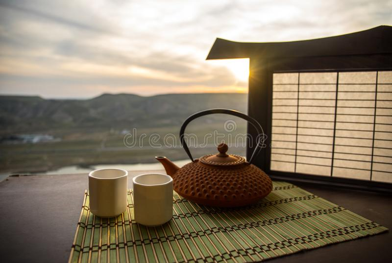 Tea concept. Japanese tea ceremony culture east beverage. Teapot and cups on table with bamboo leaves on sunset. Tea concept. Japanese tea ceremony culture east royalty free stock photos