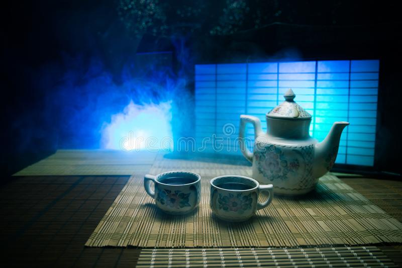 Tea concept. Japanese tea ceremony culture east beverage. Teapot and cups on table with bamboo leaves on sunset. Tea concept. Japanese tea ceremony culture east stock photo