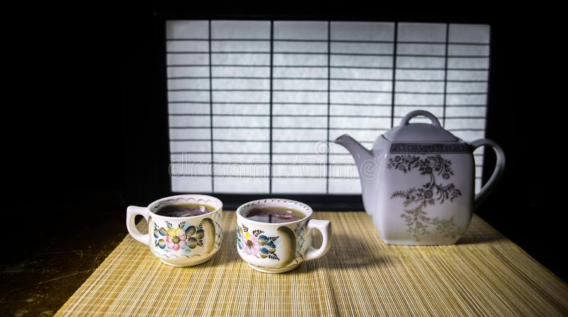 Tea concept. Japanese tea ceremony culture east beverage. Teapot and cups on table with bamboo leaves on sunset. Tea concept. Japanese tea ceremony culture east royalty free stock photography