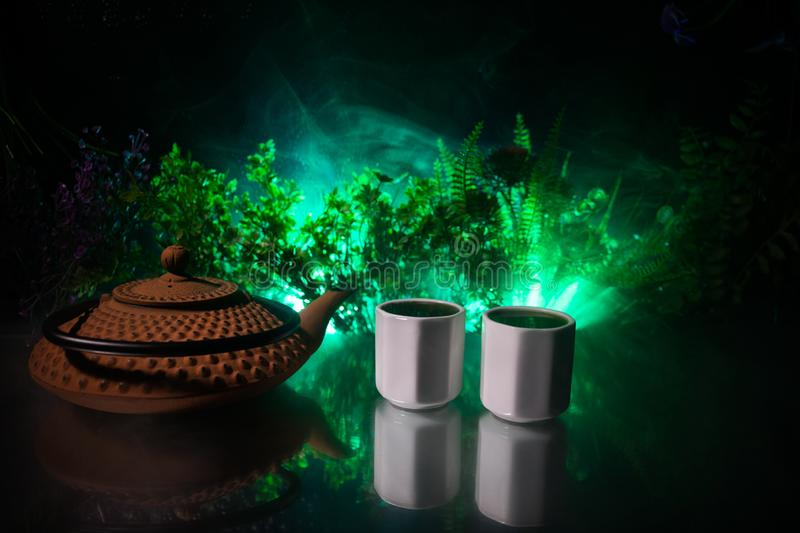 Tea concept. Japanese tea ceremony culture east beverage. Teapot and cups on table with bamboo leaves on sunset. Tea concept. Japanese tea ceremony culture east royalty free stock images
