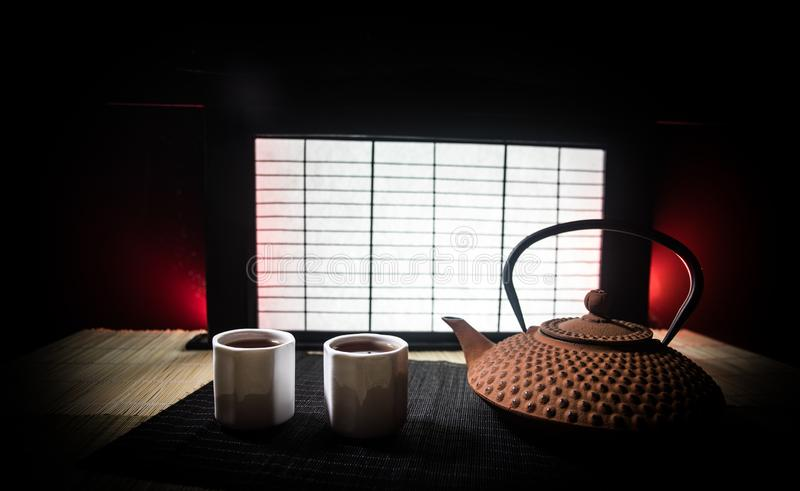 Tea concept. Japanese tea ceremony culture east beverage. Teapot and cups on table with bamboo leaves on sunset. Tea concept. Japanese tea ceremony culture east stock photography